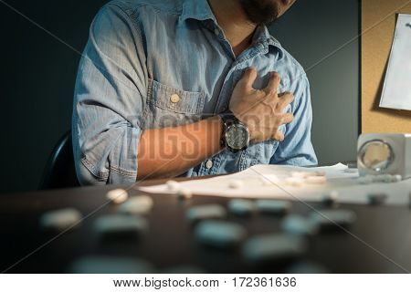 Close up of Creative editor be ill heart failure. Asian man wear eyeglasses be ill and having heart attack. Pills spilling out of pill bottle foreground.