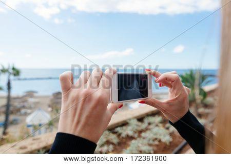 Woman photographing ocean and beach with her smartphone. Tenerife Playa del Duque Costa Adeje