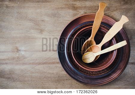 Rustic Kitchen Utensils: the Ceramic Plates and Wooden Cutlery on Wooden Background. Home Wares. Kitchen Decor in Rustic Style. View From Above With Copy Space.