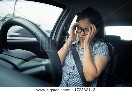 Asian glasses business woman having headache from migraine while she driving a car with bad traffic jam on rush hours. Illness exhausted disease tired for overworked concept.