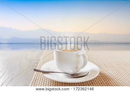white cup of hot coffee on vintage wooden table with calmness lake background in selected soft focus