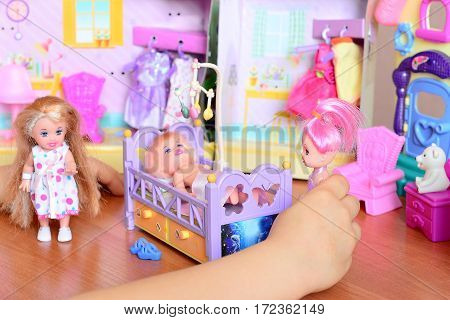 Small girl playing with dolls. Girl holding a doll in her hand. Cute dolls and toy furniture on a table. Funny game to develop children's imagination and life skills