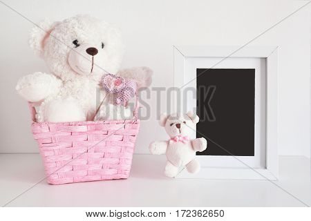 Teddy bear in a wicker basket next to a wooden photo frame. Empty copy space for Editor's content.