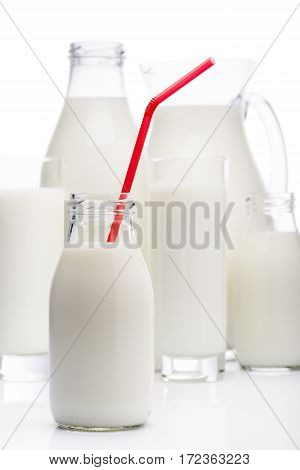 milk bottle with red drinking straw and other milk glasses on background