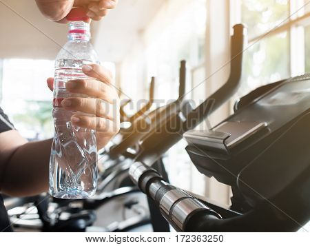 Close up fat man hands opening bottle of water on exercise bike cycling stationary exercising. Tired.