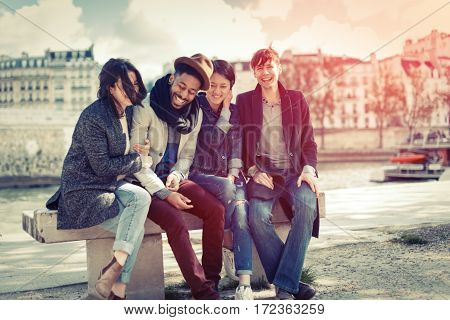 Multi-ethnic group of friends having fun in Paris along the Seine river, near Notre Dame Cathedral.