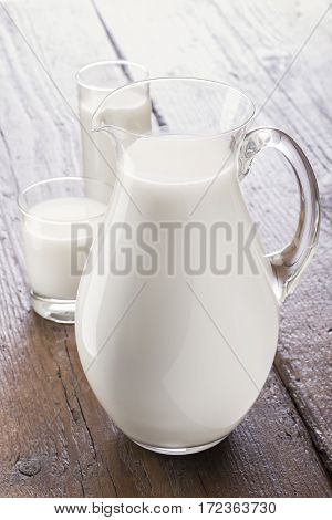 glass jug full of milk on wooden table