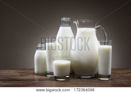 composition of bottles and glasses full of milk on wooden table.