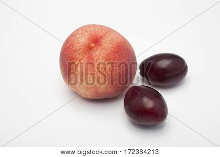 Peach and plum on a white background. Juicy peach and juicy plum. One peach and two sinks