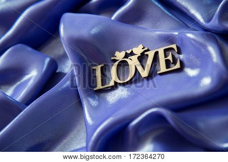background of purple, blue shiny fabric, folded pleats with the inscription love