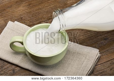 pouring milk into a green cup on wooden table.
