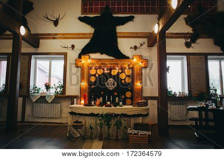 Wedding banquet interior with arch and loft bulb garland, bear skin. Rustic and country style