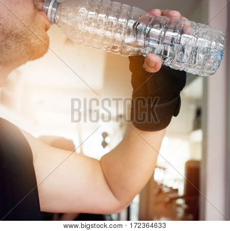 Close up man hands wear gloves holding bottle of water at a gym. People dinking water. Tired thirstily.