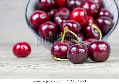 Group of cherries fallen from a ceramic bowl, on a wooden surface