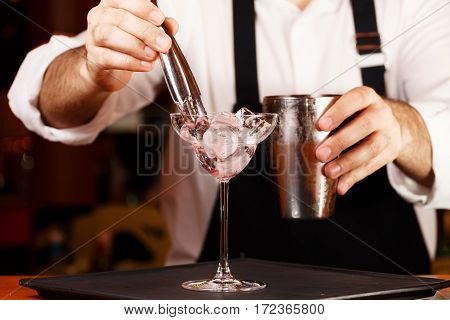 Barman In Making Cocktail At A Nightclub. Nightlife Concept. No Face. Adding Ice To Glass