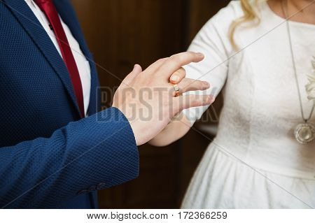 Wedding rings on hands of bride and groom. Couple in love. Dress wedding bands.