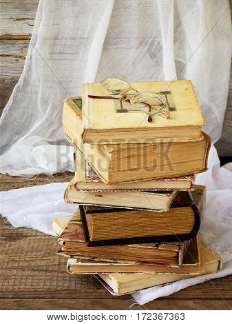 Stack Of Old Hardback Books On Wooden Background. Selective Focus. Copy Space