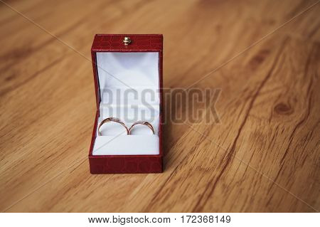 Wedding rings on red box wedding bands on wooden background