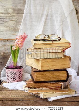 Stack Of Old Hardback Books And Hyacinth On Wooden Background. Selective Focus. Copy Space