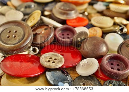 Heap of used worn colorful buttons on the wooden table as a symbolic fashion background