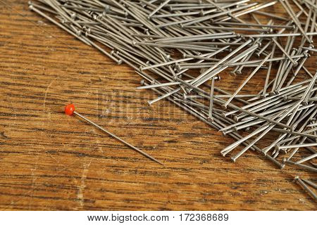 Pin with a red top separated from a heap of many silver pins used in clothing (garment) industry on the wooden background as a symbol of handmade sewing, fashion and manufacturing