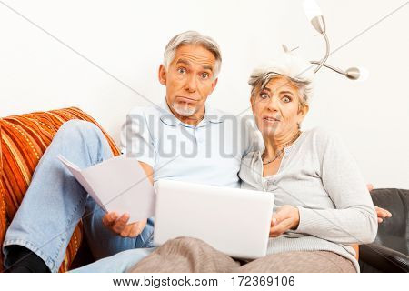 senior couple can't figure out how to use their laptop the internet