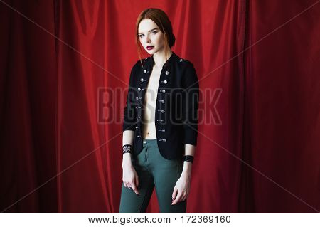 Beautiful red-haired girl in black unbuttoned jacket with bracelet on hand on red background looking at the camera. Fashion photography. Bright appearance. Red hair. Woman posing hands