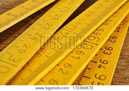 Yellow folding meter on the wooden background as a symbol of precision, craftsmanship and industrial work