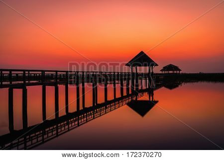 Silhouette old wooden bridge and pavilion in lake at sunset