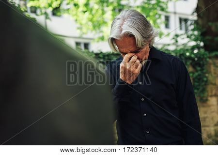 Senior man mourning by a beloved's grave