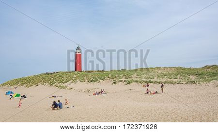 Texel, Netherlands, August 1, 2015: Texel lighthouse on the dunes in the foreground the white beach with bathers
