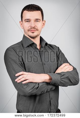 Portrait of young businessman with crossed hands over gray background.