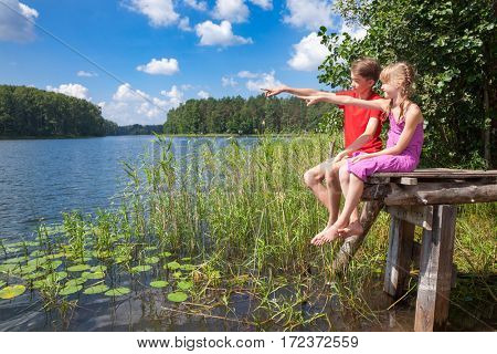 Birdwatchers boy and girl sitting on a wooden pier by a summer lake observing birds