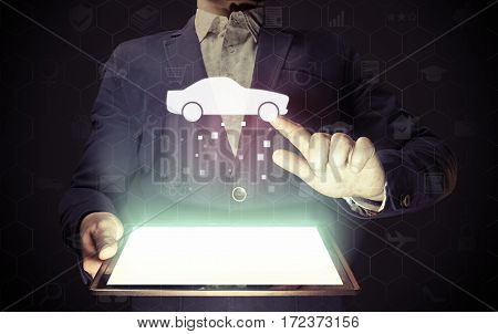 Image of a man with tablet in his hands. He looking for a car for buying or for rent using online searching service.