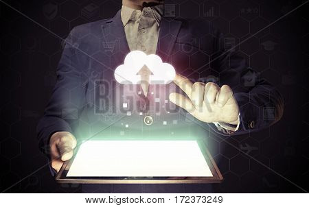 Concept of cloud storage service. Man touches to the cloud icon. He holds tablet pc that contains a many different online services.