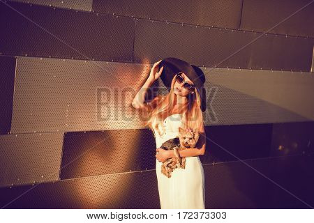 Glamorous lady in a hat and glasses holding dog puppy yorkshire terrier on street city background