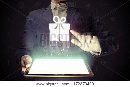Image of a man with tablet in his hands and gift icon. He chooses buys or send a gift with using online services.