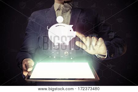 Image of a man with a tablet in his hands. He touches money box icon. Concept accumulation storage of funds internet for banking finance trading.