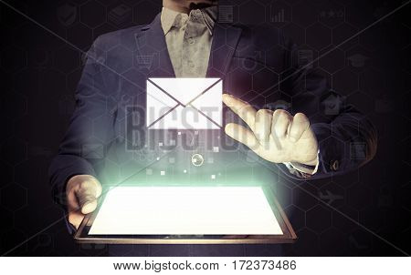 Image of a man with tablet in his hands. He are sending email by using digital tablet. Online mail correspondence feedback reporting.
