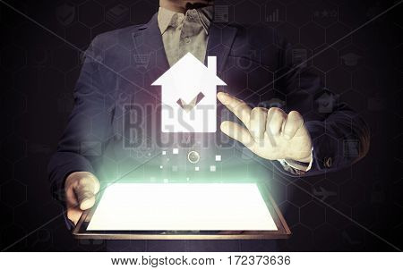 Image of a man with tablet in his hands. He looking for a house for buying or for rent using online searching service. Real estate. Online for buying or for rent.