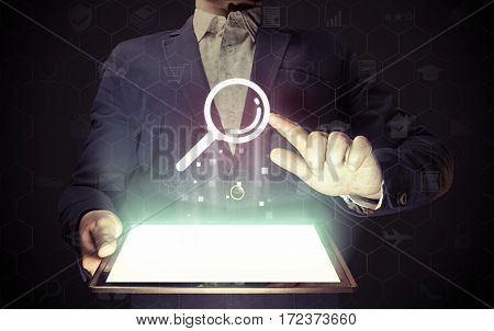 Image of a man with tablet in his hands and search icon. Сoncept search engine optimization customer support.
