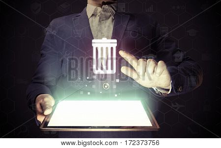 Image of a manl with tablet in his hands. He presses trash can icon. The concept of deleting files contacts putting in order cleaning service etc