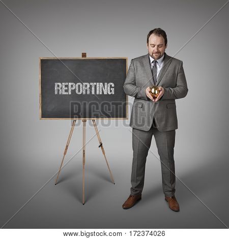 Reporting text on  blackboard with businessman and golden egg