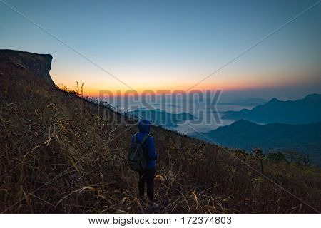Man tourist is traveling into the peak of mountain and cloudscape at Phu chi fa in Chiangrai Provice Thailand. Man traveller with hood and bag standing looking beautiful mist at sunrise. Hiking trekking concept