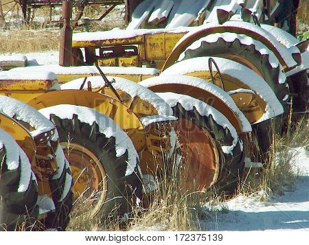 Old farm tractors covered in a light dusting of snow