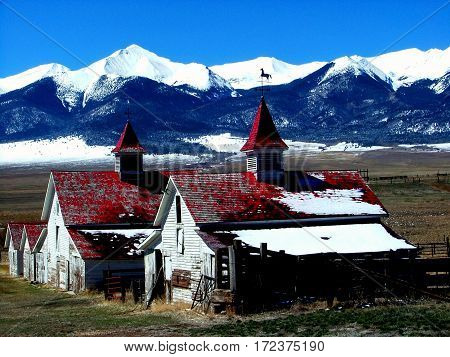 Red and white abandoned barns in Westcliff, Colorado