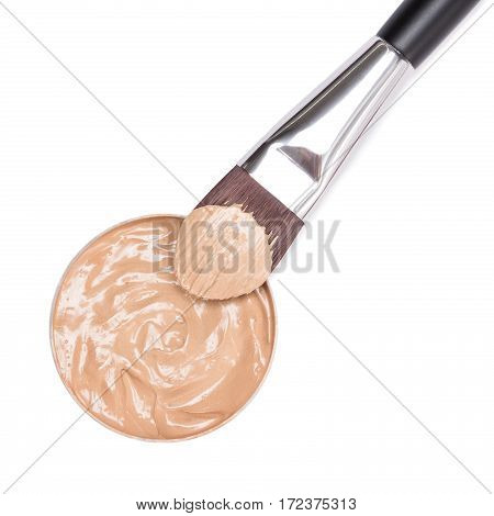 Close-up of flat make up brush and round container of makeup foundation on white background