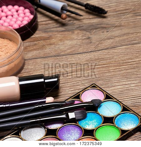 Set of basic make-up products. Concealer, bottle of foundation, powder, blush, eyeliner, mascara, colorful eyeshadow with make up brushes