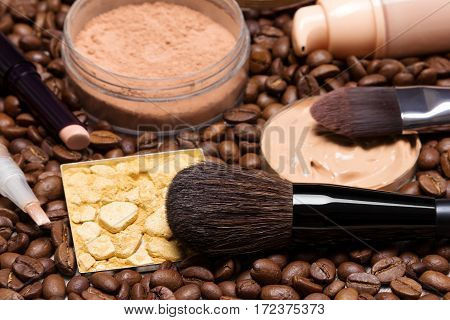 Make-up products to create fresh summer look: concealer stick, highlighter, foundation, loose and shimmer golden powder with makeup brushes on coffee beans