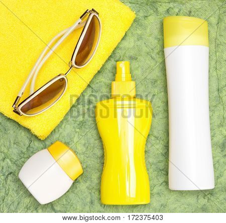 Sunscreen products for face and body skin care, towel and sunglasses. Lotion, spray and cream. Cosmetics for safe tan